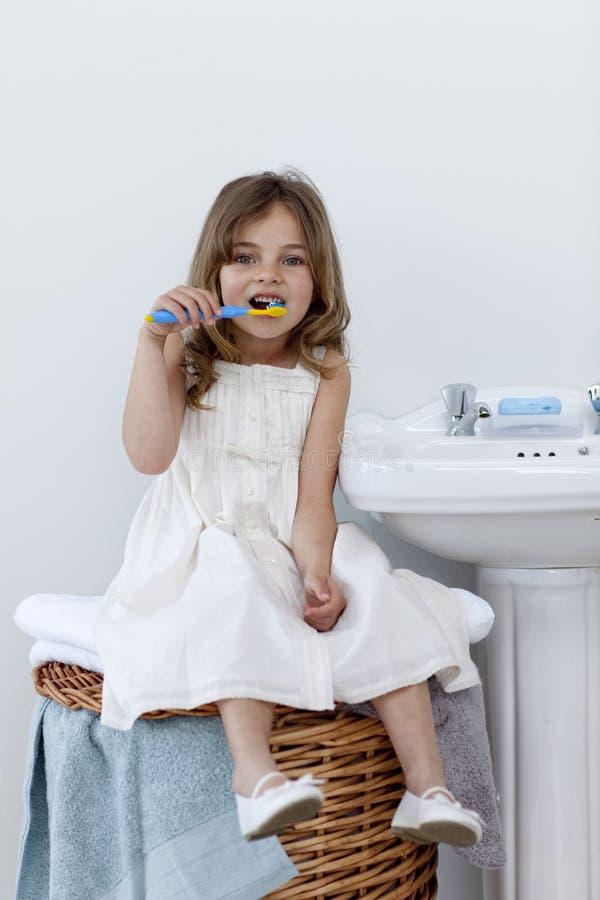 badrumcleaningdotter henne tänder royaltyfria bilder