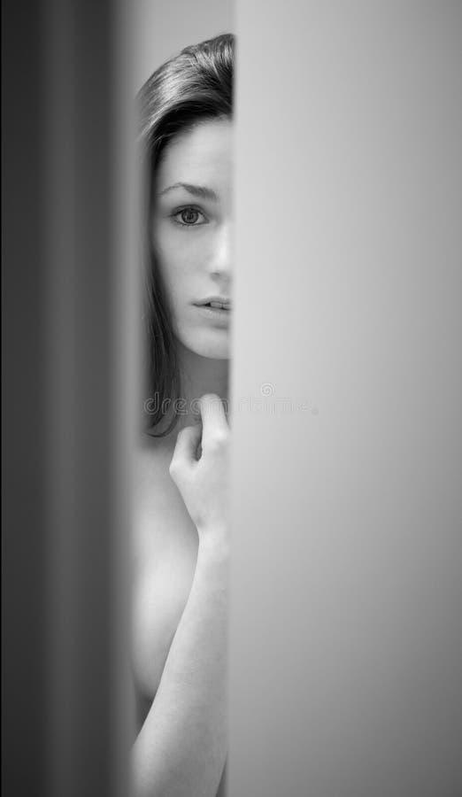 badrumdörr som kikar ut den förvånada kvinnan royaltyfria bilder
