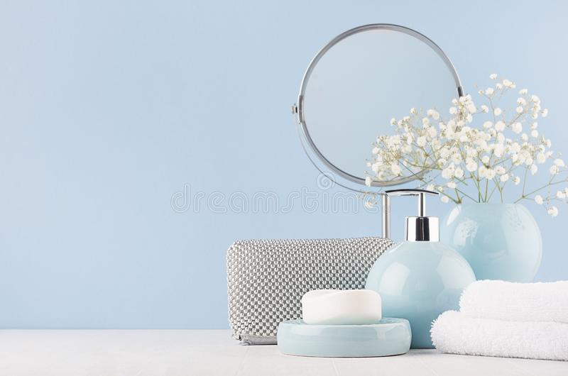 Badrumdekoren för kvinnlig i ljusa mjuka blått färgar - cirkla spegeln, den kosmetiska påsen för silver, vita blommor, handduken, arkivbild
