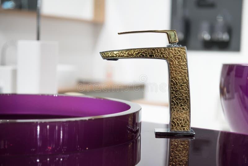 Badrumdetalj i nytt lyxhem: vask och guld- vattenkran royaltyfri fotografi