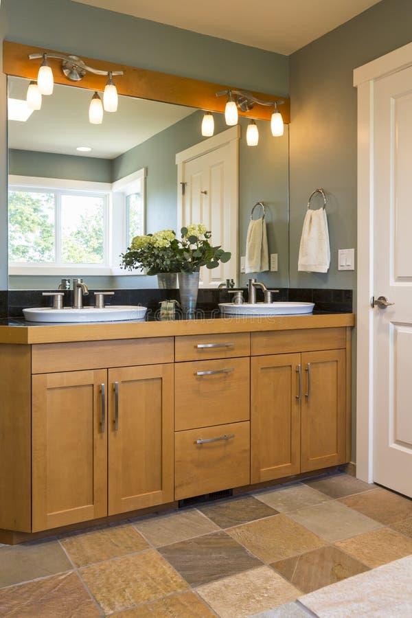 Badrumfåfänga med wood kabinetter, dubbla vaskar, kritiserar tegelplattagolv och brytningbelysning i modern exklusiv hemmiljö arkivbilder