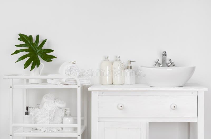 Badruminre med den vita väggen, tappningmöblemang, handdukar och vasken arkivfoto