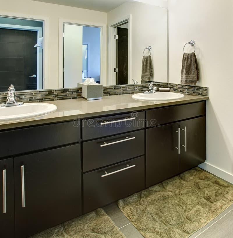 Badruminre med svarta kabinetter, två vaskar och den stora spegeln royaltyfria bilder