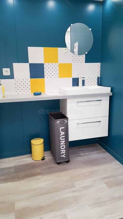 badrummet med en liten rund spegel och en smutsig tvätteri slänga i soptunnan royaltyfri bild