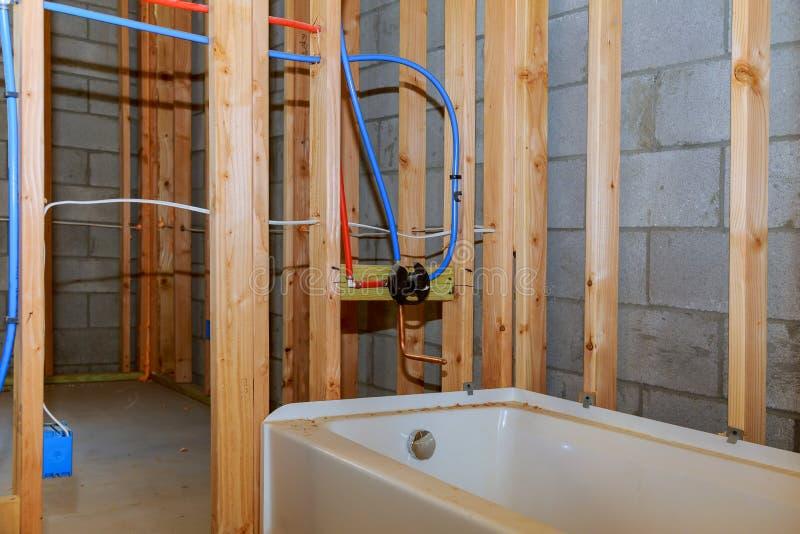 Badrummet omdanar visning under förbindande installation för golvrörmokeriarbete av rör för vatten för nybyggen royaltyfri bild