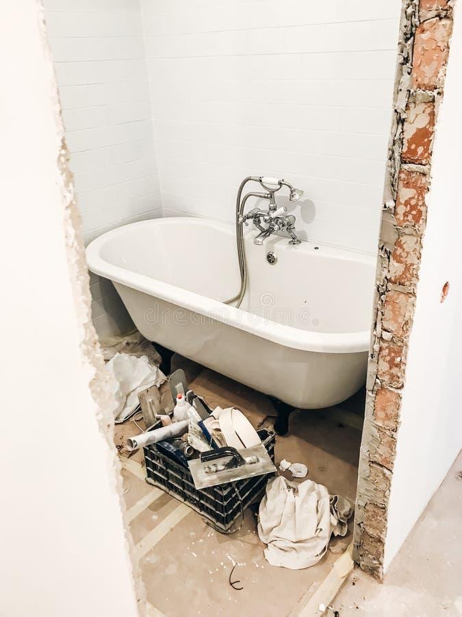 Badrumrenoveringbegrepp stilfullt vitt badkar och retro fau royaltyfri bild