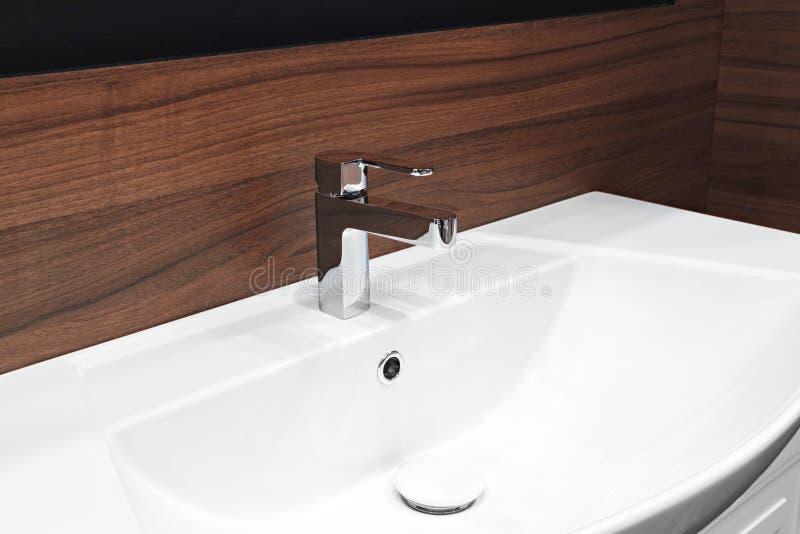Badrumsvart och röd brun träinre med den vita vasken och den moderna stilvattenkranen arkivfoton