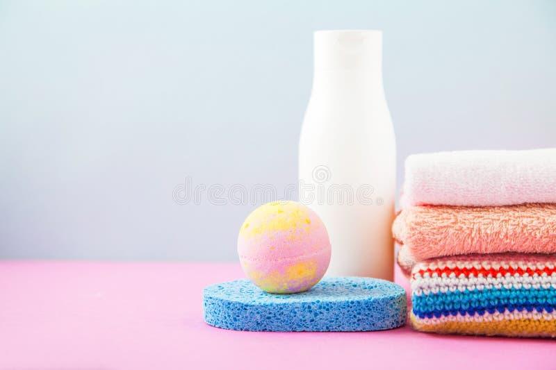Badrumtillbehör - handdukar och schampon, badskum, kräm på ett ljus, ljusa blått och rosa färgbakgrund begreppet av att att bry s royaltyfria foton