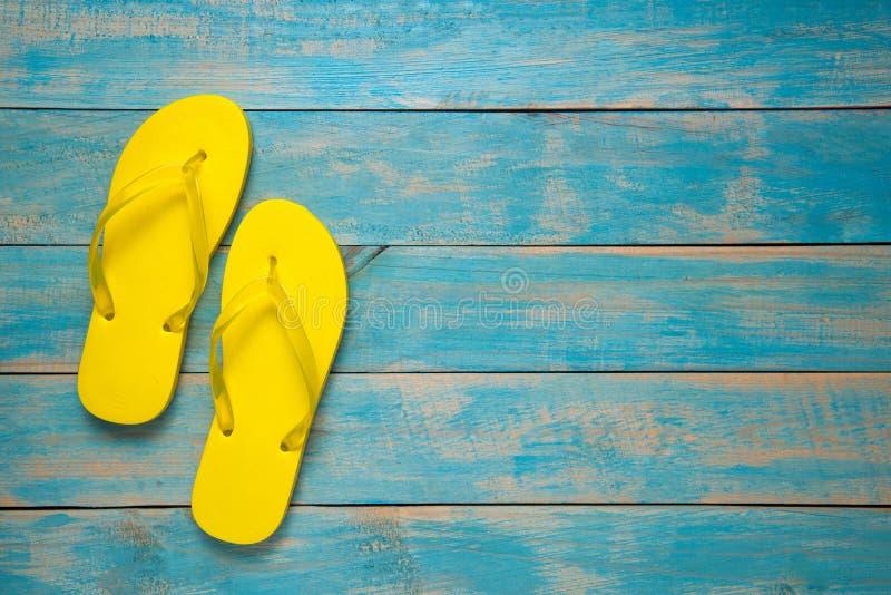 Badsko sandal, sommar Gula sandaler för flipmisslyckande på blått trä royaltyfri bild
