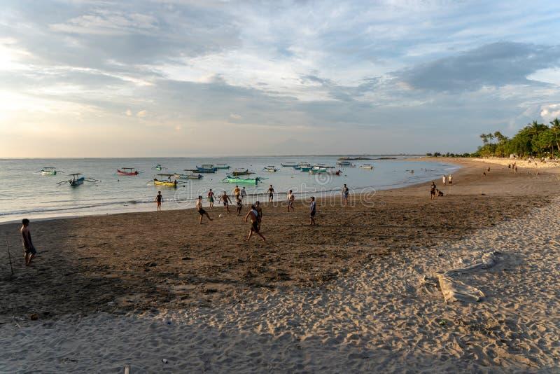 BADUNG,BALI/INDONESIA-APRIL 02 2019年:亚洲少年戏剧橄榄球或足球在海滩与日落或金黄小时背景 库存图片