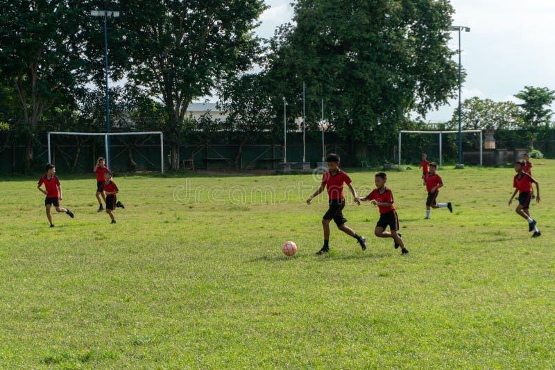 BADUNG,BALI/INDONESIA-APRIL 05 2019年:小学生戏剧橄榄球或足球在领域与红色球衣 库存照片