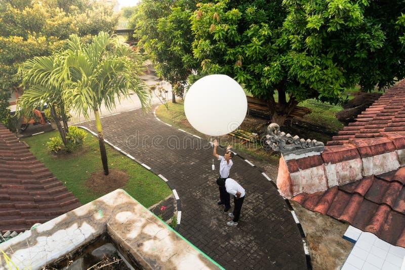 BADUNG/BALI- 10-ОЕ АПРЕЛЯ 2019: Наблюдатель на станции Ngurah Rai метеорологической выпуская большой белый воздушный шар sonde ра стоковое изображение