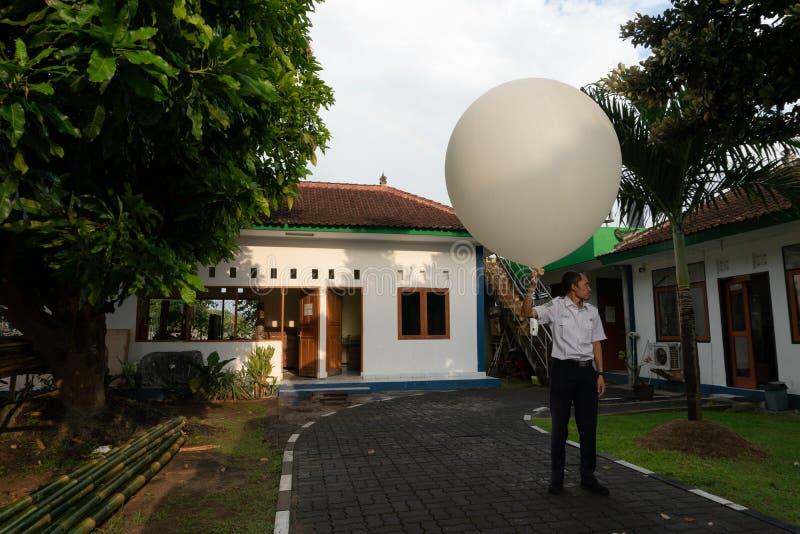 BADUNG/BALI- 10-ОЕ АПРЕЛЯ 2019: Наблюдатель на станции Ngurah Rai метеорологической выпуская большой белый воздушный шар sonde ра стоковое фото rf
