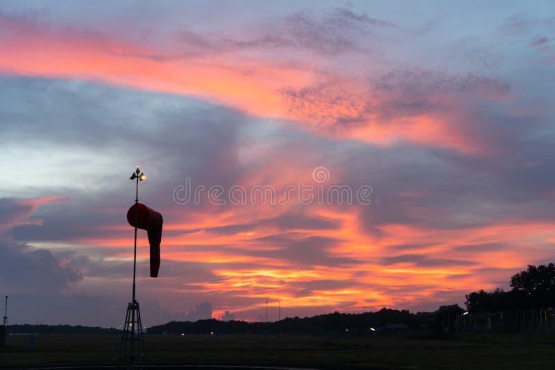 BADUNG/BALI-APRIL 14 2019年:下风向袋在黎明在与触毛和积云的红色橙色发光的天空下 库存图片