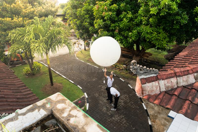 BADUNG/BALI-APRIL 10 2019年:发布大白色无线电sonde气球的拉伊巴克罕气象站的一名观察员测量 库存图片