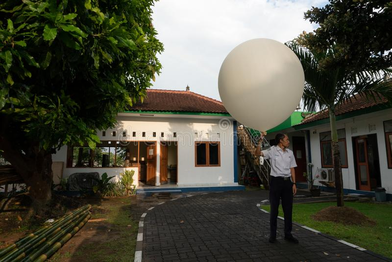 BADUNG/BALI- 10 AVRIL 2019 : Un observateur ? la station m?t?orologique de Ngurah Rai lib?rant le grand ballon par radio blanc de photo libre de droits