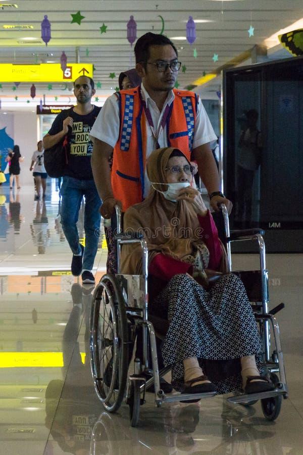 BADUNG/BALI- 25 DE JUNIO DE 2018: El equipo de vuelo ayuda a los pasajeros enfermos que usan una silla de ruedas fotos de archivo libres de regalías