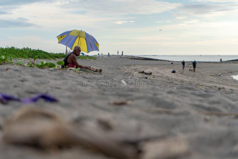 BADUNG, BALI/INDONESIA- 2. APRIL 2019: Alter Mann sitzt auf dem Sand und genießt ein Sonnenbad zu nehmen lizenzfreie stockbilder