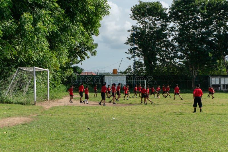 BADUNG, BALI/INDONESIA- 5 DE ABRIL DE 2019: Fútbol o fútbol elemental del juego del estudiante en el campo con el jersey rojo foto de archivo libre de regalías