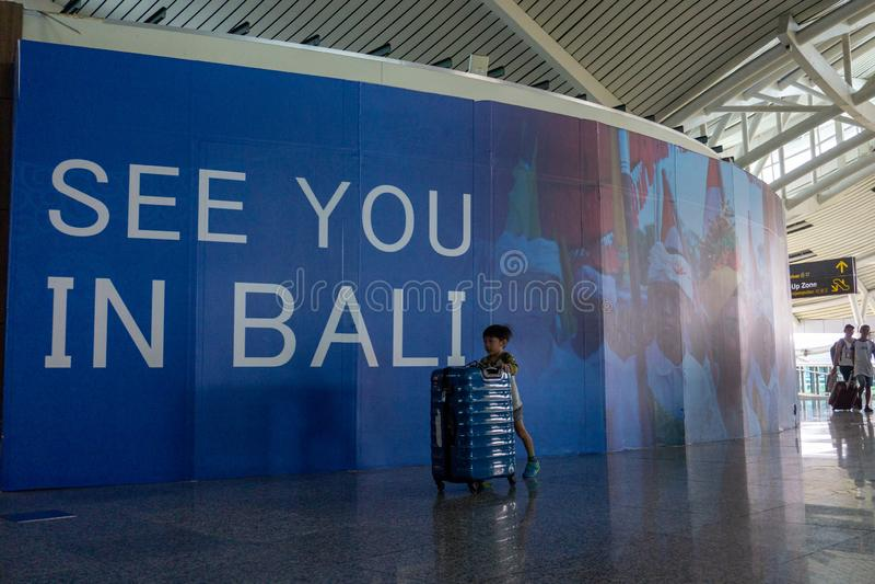 BADUNG, BALI/INDONESIA- 25 de junio de 2018: El niño pequeño trae su propia maleta solamente al terminal de la salida en Ngurah R fotografía de archivo libre de regalías