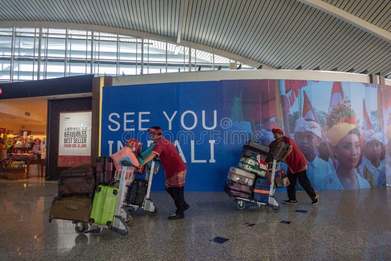BADUNG, BALI/INDONESIA- 25 de junio de 2018: Los porteros traen las maletas del pasajero al terminal de la salida fotografía de archivo
