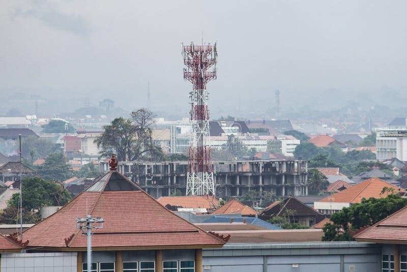 BADUNG BALI/INDONESIA: Ett telekommunikationtorn som lokaliseras i Bali, ser högt än de omgeende byggnaderna royaltyfri foto