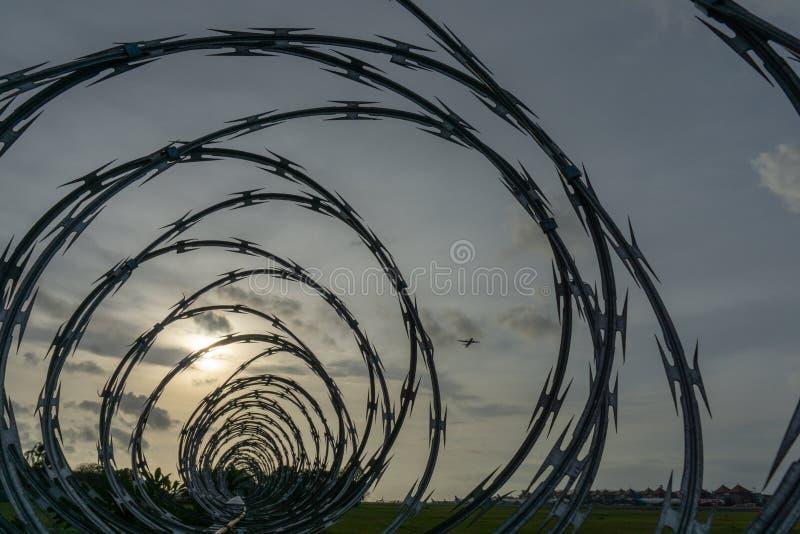 BADUNG BALI/INDONESIA-JANUARY 01 2017: Flygplatssikten från de försåg med en hulling staketen, när solen går ner royaltyfri fotografi