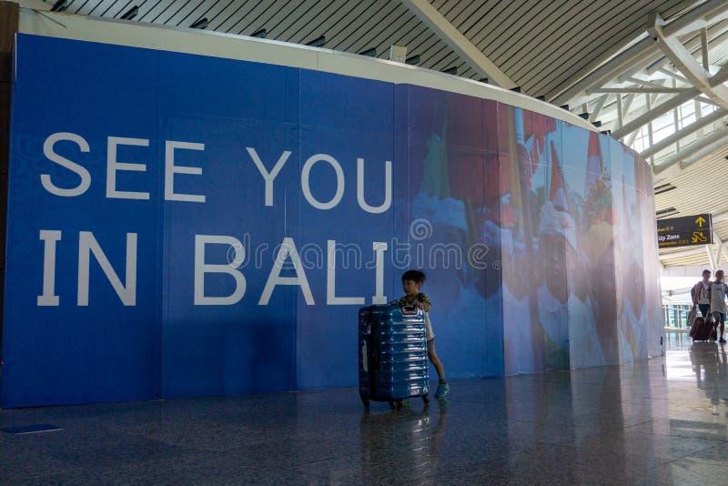 BADUNG, 25 BALI/INDONESIA-Juni 2018: Weinig jongen brengt zijn eigen koffer alleen aan vertrekterminal in Ngurah Rai Bali royalty-vrije stock fotografie