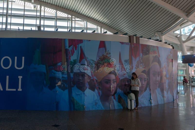 BADUNG/BALI-MARCH 28 2019: Żeński turysta, niesie walizkę, stał w terenie w balijczyka ornamentacyjnym lotnisku, fotografia stock