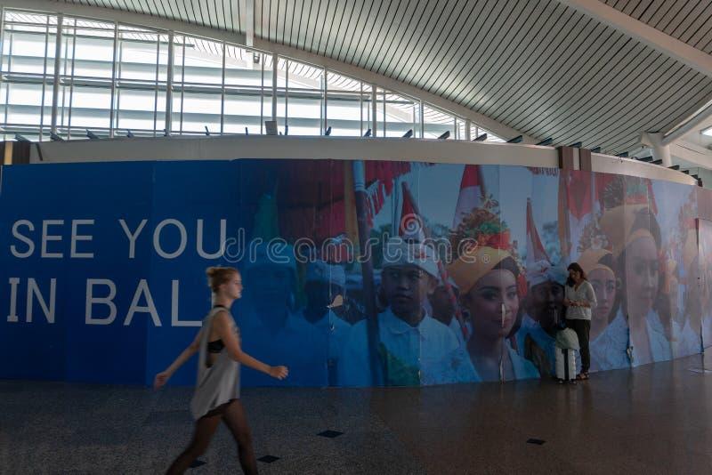 BADUNG/BALI-MARCH 28 2019: En kvinnlig turist som b?r en resv?ska, stod i ett omr?de i en dekorativ flygplats f?r Balinese, royaltyfria foton