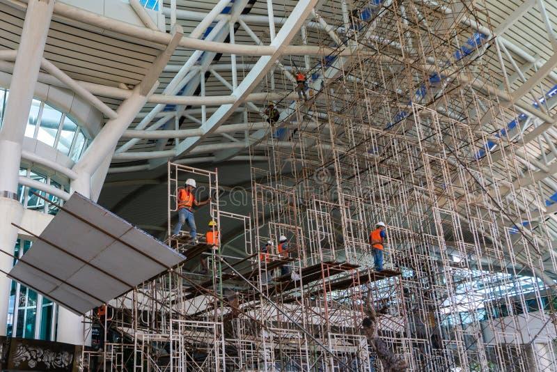 BADUNG/BALI-MARCH 28 2019: N?gra arbetare s?tter tillsammans ett material till byggnadsst?llning p? flygplatsens den internatione royaltyfri foto