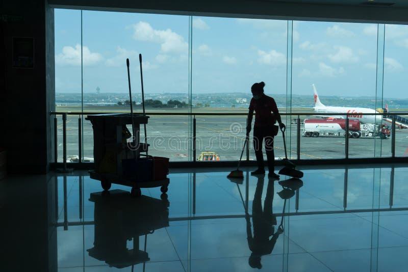 BADUNG/BALI- 28 MARZO 2019: la siluetta di un portiere sta pulendo il pavimento terminale di partenza con il fondo e il airpo del fotografia stock libera da diritti