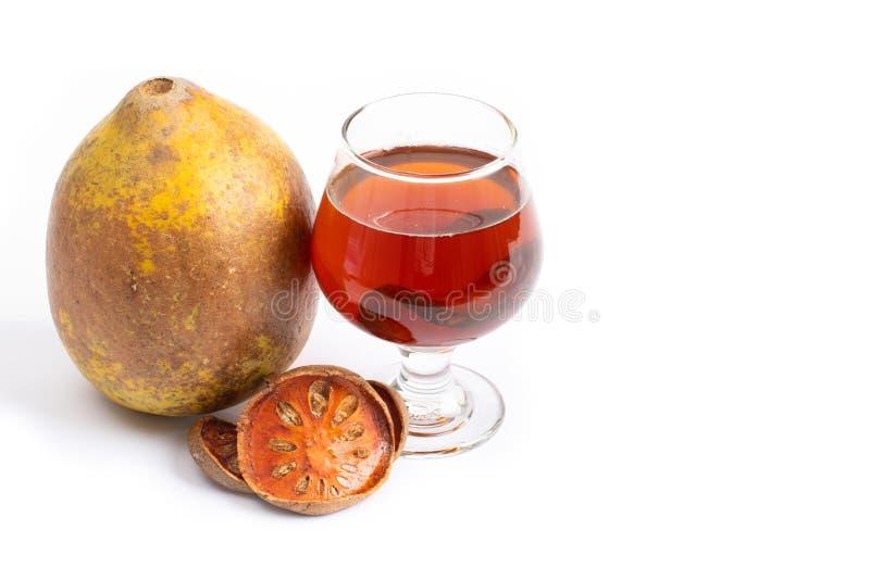 Bael-Fruchttee - ein Glas Bael-Fruchttee und -Trockenfr?chte des Ballengetr?nkes lizenzfreie stockfotos