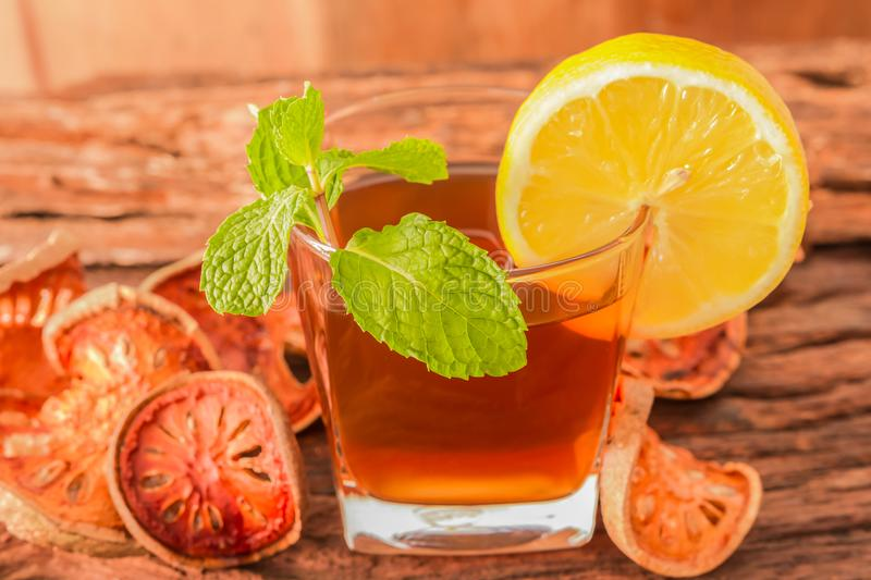 Bael fruit tea - A glass of Bael fruit tea with lemon slices and mint leaf royalty free stock photos