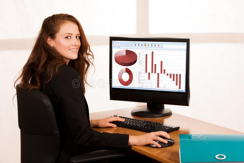 Baeutiful young business woman working at her desk in the office royalty free stock photography