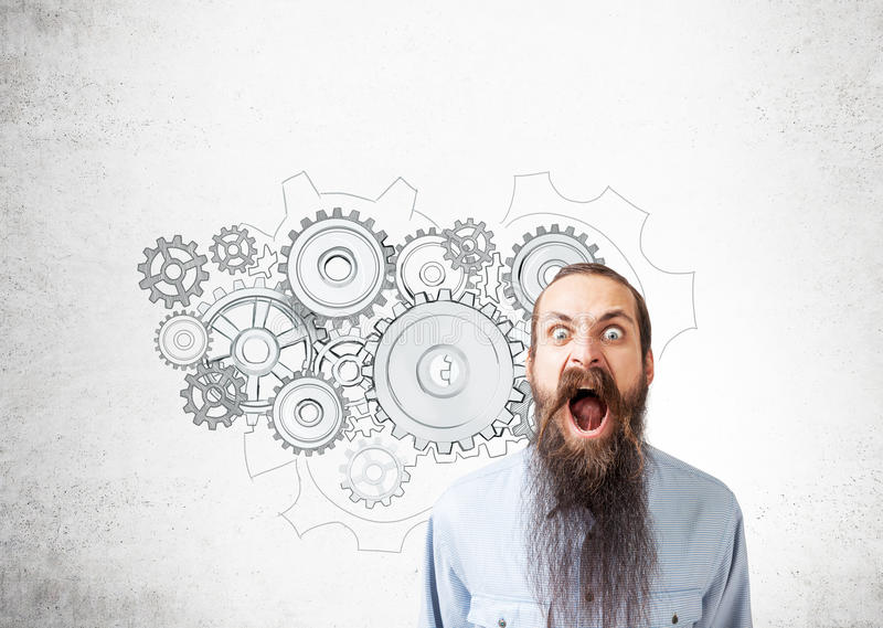 Baffled man and gear sketches. Portrait of a baffled man with a long beard screaming while standing near a concrete wall with gear sketches on it stock photography