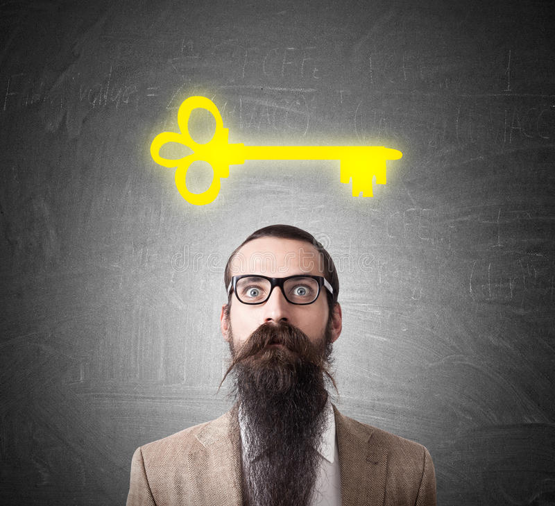 Baffled man and large yellow key sketch. Baffled man wearing glasses and long beard is standing near blackboard with large yellow key sketch depicted on it royalty free stock images