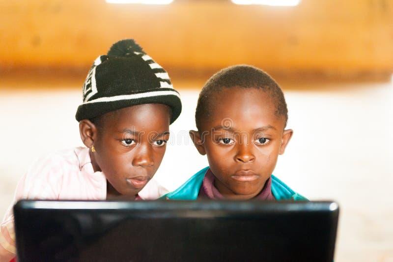 Bafoussam, Камерун - 6-ое августа 2018: африканские дети, в классе смотря экран компьтер-книжки уча использовать новую технологию стоковые фотографии rf