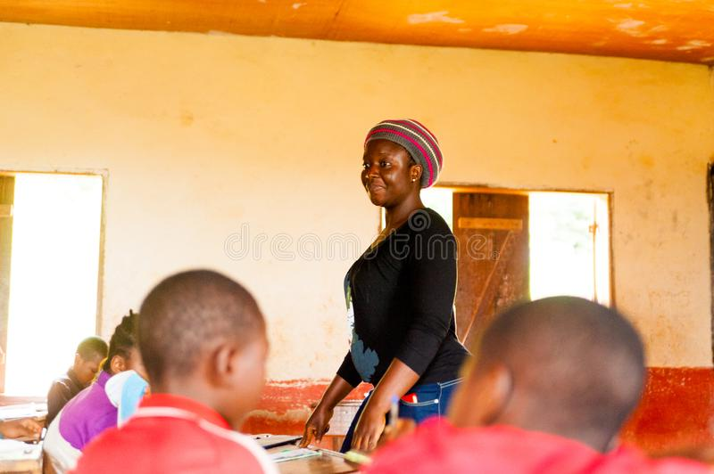 Bafoussam, Cameroon - 06 august 2018: young african girl teacher volunteer smiling during lessonstanding up among children stock images