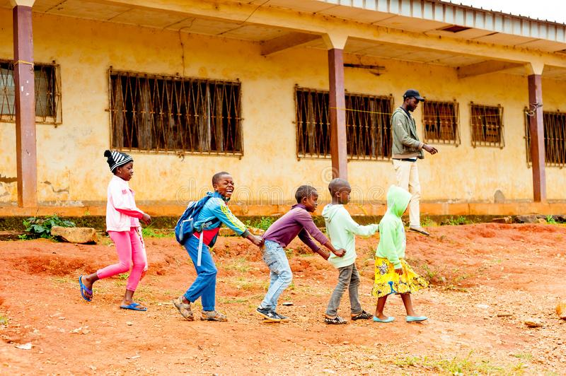 Bafoussam, Cameroon - 06 august 2018: young smiling african pupils playig and having fun outside poor village school during summer royalty free stock photography