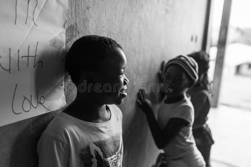 Bafoussam, Camerun - 6 agosto 2018: ritratto in bianco e nero del ragazzo africano sorridente allegro in aula con l'altro gioco d fotografie stock