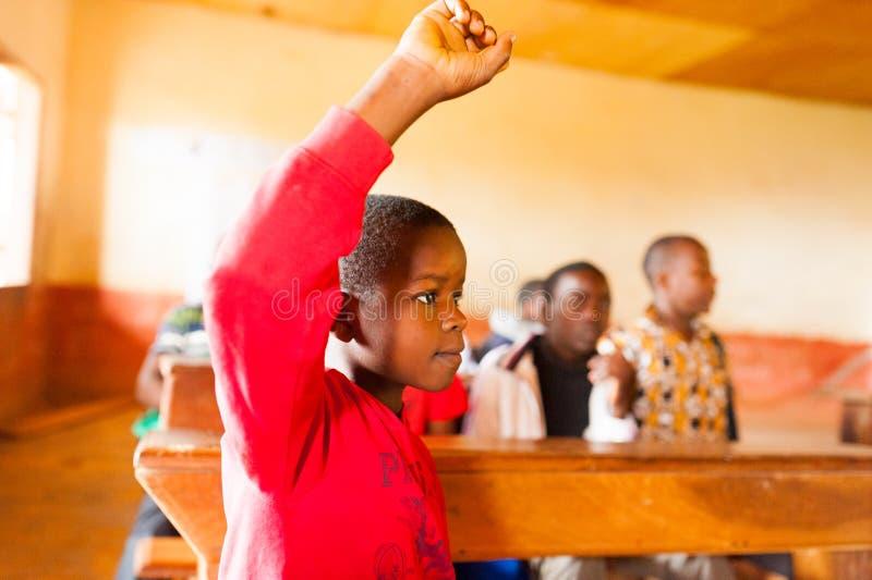 Bafoussam, el Camerún - 6 de agosto de 2018: alumno africano activo implicado en sala de clase durante la lección en escuela del  fotografía de archivo