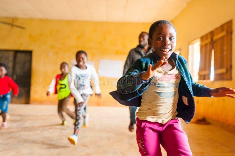 Bafoussam, Kameroen - 06 augustus 2018: jongelui die Afrikaanse meisjes en jongens glimlachen die en de schooldurin in werking st royalty-vrije stock fotografie