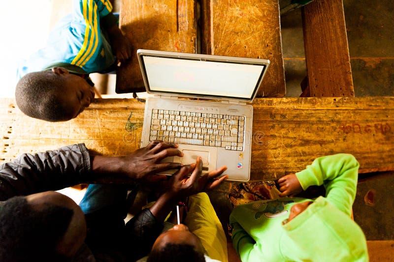 Bafoussam, República dos Camarões - 6 de agosto de 2018: acima da ideia de crianças africanas e de ensino do professor como usar  foto de stock royalty free