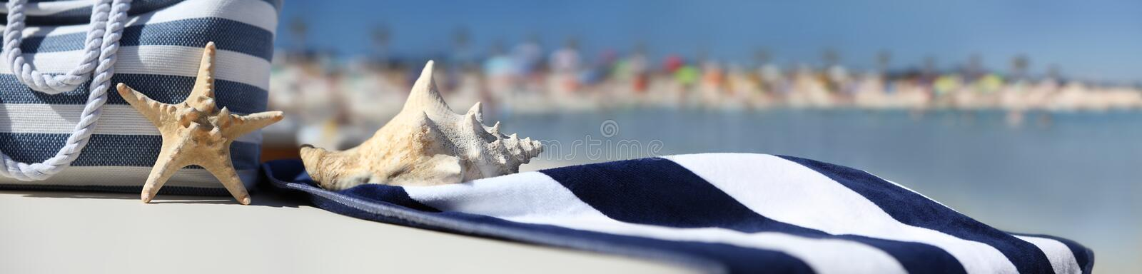 Bag on the beach with starfish, shell and blue towel stock image
