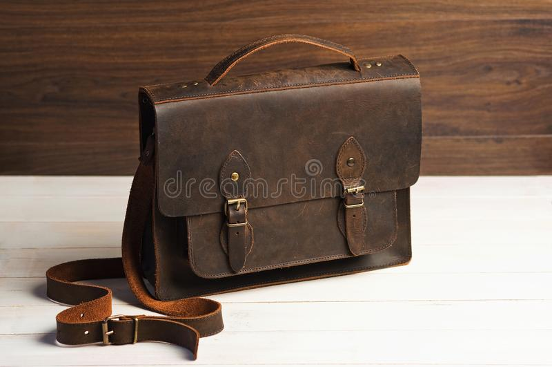 Bag briefcase for businessman men, leather brown bag on a wooden background. Men`s fashion, accessory, business background. royalty free stock image