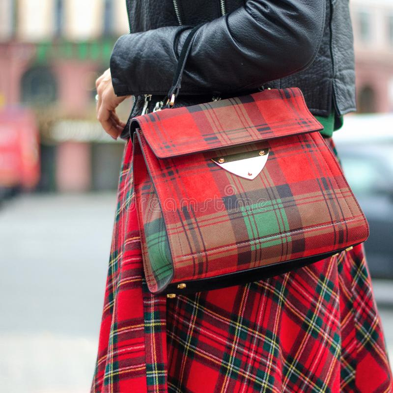 Bag closeup in female hands. Bright image, style. Girl in a red plaid skirt.  royalty free stock photos