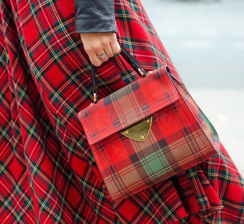 Bag closeup in female hands. Bright image, style. Girl in a red plaid skirt.  royalty free stock photography