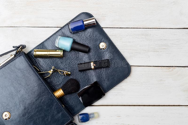 Bag of dark blue color and cosmetics on a white wooden background. Flat lay. Bag of dark blue color and cosmetics on a white wooden background. View from above stock image