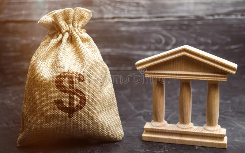 A bag with dollar money and a bank or government building. Deposits, investment in the budget. Grants and subsidies. Payment of stock photography